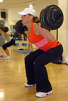 A female excercises during a pump class.