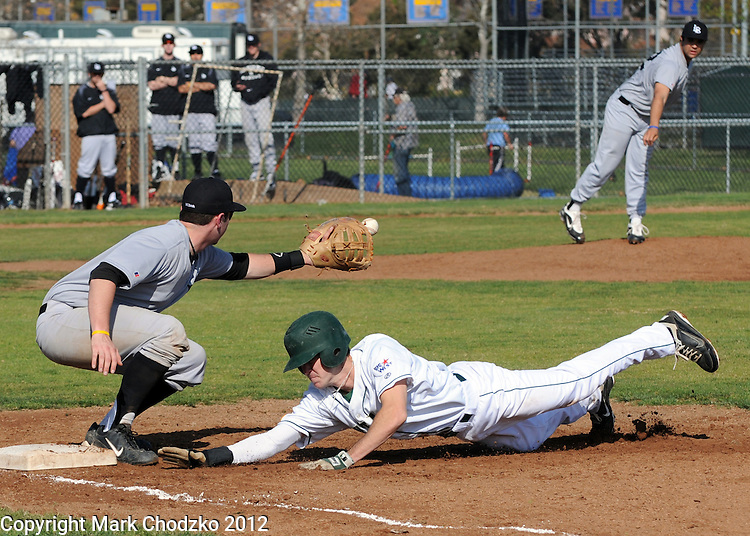 Baseball player dives headfirst back to first base on a pickoff attempt.