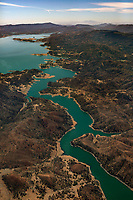 aerial photograph of Putah Creek, also known as the Green River because of the build up of algae and vascular plants, where it flows into Lake Berryessa, Napa County, California toward the south.  Mount Diablo is visible on the horizon.