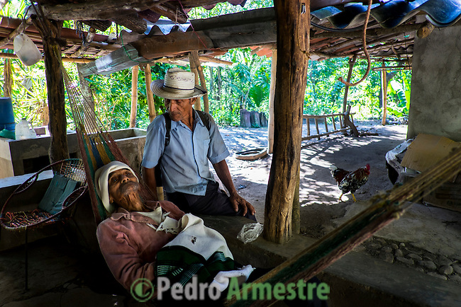 """November 10, 2014. """"Water it´s the real thing""""<br /> Ernesto Montes with his neighbour, Santos Rodriguez, in his house in Nejapa (El Salvador). He has the illnes of Chikungunya and he doesn' t have drinking water at home. The people of Nejapa in El Salvador, have no drinking water because the Coca -Cola company overexploited the aquifer in the area, the most important source of water in this Central American country. This means that the population has to walk for hours to get water from wells and rivers. The problem is that these rivers and wells are contaminated by discharges that makes Coca- Cola and other factories that are installed in the area. The problem can increase: Coca Cola company has expansion plans, something that communities and NGOs want to stop. To make a liter of Coca Cola are needed 2,4 liters of water. ©Calamar2/ Pedro ARMESTRE"""