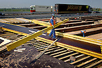 """Langs de snelweg A27 bij Noordeloos werken medewerkers van Ballast Nedam aan een nieuw viaduct. Vanwege slijtage en ouderdom van het oude, wordt naast de snelweg een nieuw en breder kunstwerk gebouwd dat tijdens de bouwvak op zijn plaats geschoven gaat worden. Omdat het viaduct er aan beide zijden zeven meter bij krijgt, wordt tevens de onderbouw van de betonnen plaat verbreed. Het slopen van het oude, en het op zijn plaats leggen van het nieuwe moet in de zomer in negen dagen klaar zijn..© Ton Borsboom.editorial; Nederland; Europa; bouwaannemer; bouwactiviteit; bouwaktiviteit; bouwbedrijf; bouwindustrie; bouwkosten; bouwlieden; bouwnijverheid; bouwonderneming; bouwplaats; bouwproject; bouwput; bouwsector; bouwterrein; bouwvakker; bouwvakkers; utiliteitsbouw; beton; """"Nederland, Europa, editorial""""; """"arbo, arbeidsomstandigheden, veilig, onveilig""""; arbo, veiligheidsvest, reflectie, hesje""""; """"tilen, rugbelasting, rug, zwaar, via""""; """"gww, grondwerk, wegenbouw"""";"""