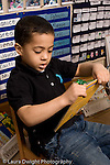 Preschool Headstart 3-5 year olds boy sitting in chair looking at picture book vertical