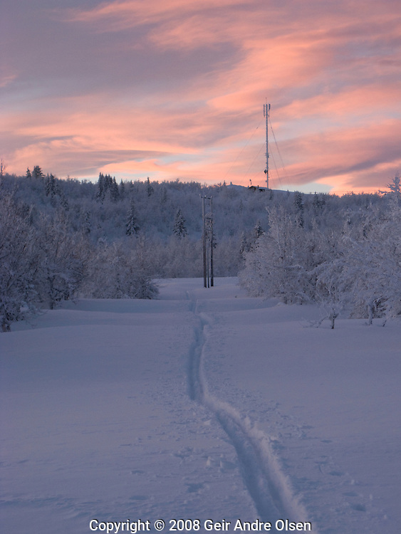 Going towards an antenna in the sunset on a beautifull winters day at Venabygdsfjell, Norway