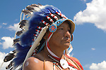 A close up of an Indian Chief dressed in full regalia, and on horseback, pauses for a moment against a vibrant Montana blue sky for picture taking after performing the reenactment of the annual Battle of the Little Bighorn in Hardin Montana. Model Release