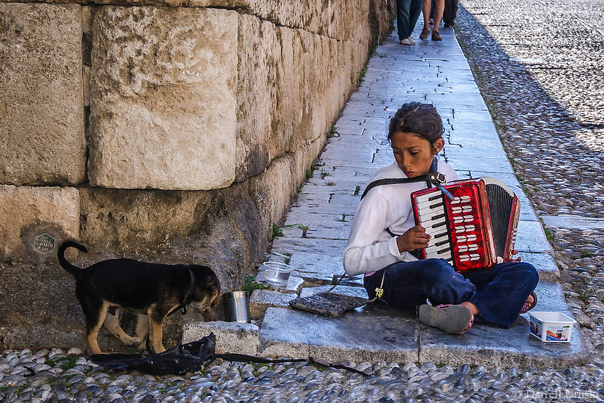 Fine Art Print Photograph, of a young girl and her dog, busking on a street corner in Rhodes, Greece.
