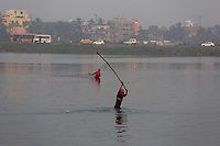 Fisherman striking water with sticks to encourage fish to rise to the surface.<br /> <br /> To license this image, please contact the National Geographic Creative Collection:<br /> <br /> Image ID: 1925804 <br />  <br /> Email: natgeocreative@ngs.org<br /> <br /> Telephone: 202 857 7537 / Toll Free 800 434 2244<br /> <br /> National Geographic Creative<br /> 1145 17th St NW, Washington DC 20036