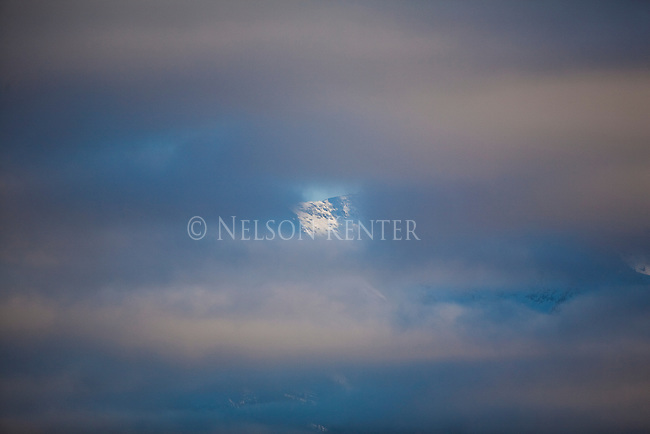 Clouds almost cover a mountain peak peeking hrough