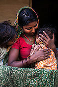 21 year old Asha Devi holds her 11 month daughter, Sita Mandal while her 3 year old son, Gaurav Mandal (left) looks on in her house in Bhardaha in Saptari, Nepal.