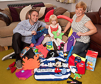 Young Florence Cuthbert isn't quite two, but she was pleased to receive an early birthday present in the shape of a pile of swimming goodies from Computershare Voucher Services. Florence is pictured with her parents Jeremy and Kate.