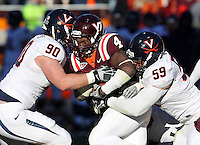 Nov 27, 2010; Charlottesville, VA, USA; Virginia Tech Hokies running back David Wilson (4) is tackled by Virginia Cavaliers defensive end Jake Snyder (90) and Virginia Cavaliers defensive tackle John-Kevin Dolce (59) during the game at Lane Stadium. Virginia Tech won 37-7. Mandatory Credit: Andrew Shurtleff