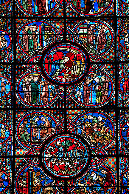 Medieval stained glass Window of the Gothic Cathedral of Chartres, France - dedicated to the Life of St Lubin . Central bottom panel shows A barrel of wine being transported to the Cathedral, below left - The young Lubin working as a shepherd, below right - A monk gives Lubin a belt with the alphabet written on it, above left - Lubin receiving instruction from a cleric, above right - Lubin spends his spare time learning to read, while his companion idles.  Top central panel -  A cellerer draws sacramental wine into a cruet, below left - Lubin is accepted into a monastery, below right - Nileffus advises Lubin to visit other monasteries to broaden his knowledge, above left - Lubin, Nileffus and another monk, approach a new monastery, above right - Lubin and his companions leaving a monastery. A UNESCO World Heritage Site.