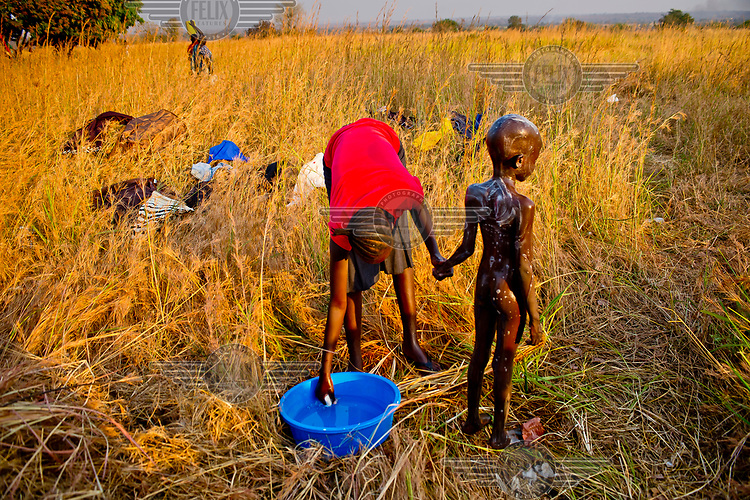 A South Sudanese refugee washes her child in Dzaipi transit centre where 8.5 litres of water was available per person per day.
