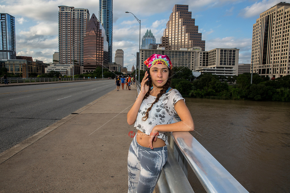Local Austin woman talking on mobile smartphone call on the Congress Avenue Bridge against the Austin Skyline. The Texas State Capitol can be seen in the distance.