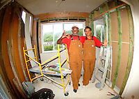 Two men working on a home improvement project with tan overalls and scaffolding taken with a fish eye lens