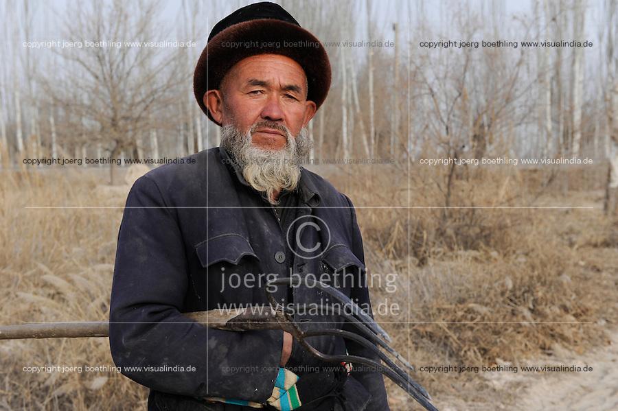 Asien CHINA Provinz Xinjiang Kashgar , uigurischer Bauer im Winter / CHINA province Xinjing Kashgar , uyghur farmer with fork during winter