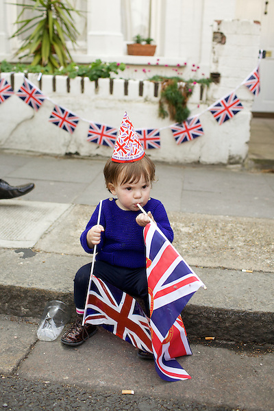 A young girl plays with Union Jack flags during a street party to celebrate the wedding of Prince William and The Duchess of Cambridge