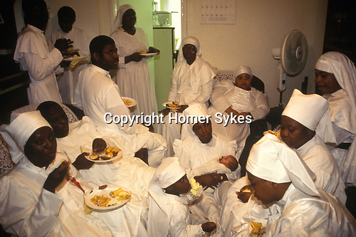 Brixton, London. 1990's <br /> The Church of the Brotherhood of the Cross and Star. A 'feast' in a members new home is followed by a 'home blessing' service. <br /> This semi Christian Nigerian church was founded by Olumba Olumba Obu known as OOO. His members worship him and Christ. He believes that he is the eighth and final reincarnation of the Godhead.