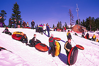Children snow tubing down a Mountain Slope in Mount Seymour Provincial Park, in the Coast Mountains, North Vancouver, Southwestern British Columbia, Canada