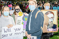 """A crowd gathers in Boston Common for the 2020 Women's March protest in opposition to the re-election of US president Donald Trump in Boston, Massachusetts, on Sat., Oct. 17, 2020.<br /> The signs here read """"Will you shut up man?"""" (a reference to Democratic presidential candidate and former Vice President Joe Biden's line to US president Donald Trump during the first presidential debate), """"Cast your spell,"""" and """"I dissent"""" featuring a picture of recently-deceased Supreme Court Justice Ruth Bader Ginsburg."""