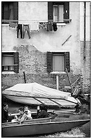 Four people in a small boat passing a building with washing hanging outside, Venice, Italy.