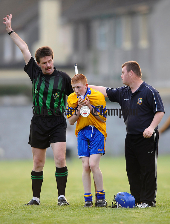 The linesman calls for help for Sixmilebridges Paul Finnan as Ronan Keane  helps out