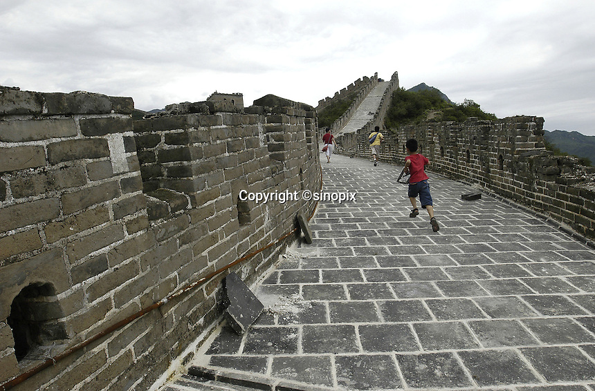 Three children cilmb onto the Huanghuacheng section of the Great Wall in suburban Beijing, China. Beijing began repairing a 12.4 kilometer section of the Ming-era Great Wall at cost of 12 million yuan(US$1.45 million) from this March..16-JUL-04
