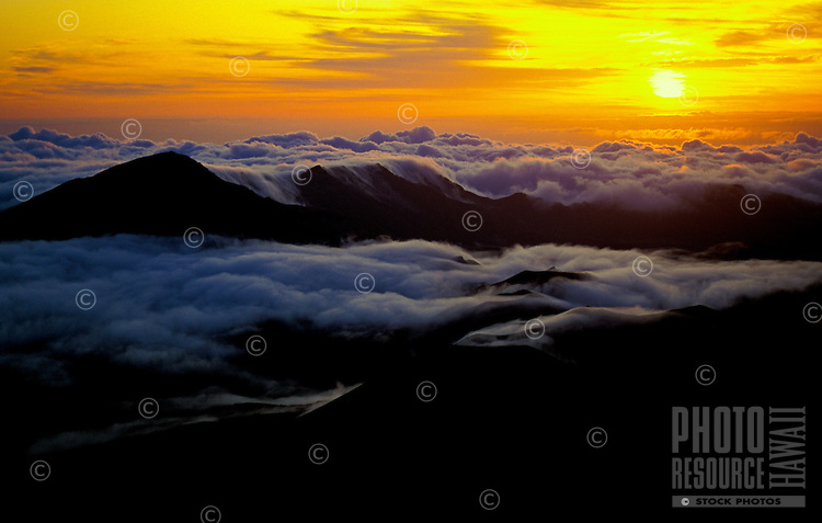 Sunrise from atop Haleakala at a 9,745-ft. elevation in Haleakala National Park. Sky catches fire with color as cascading waterfalls of clouds stream down distant ridge lines seven miles away. Clouds roll in partially engulfing cinder cones as tall as 1,100 ft.