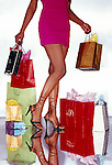 Lower torso of woman with shopping bags
