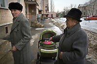 An elderly couple dressed up for family celebration walks with their grandchild in the snow in Oryol, a poor city in the heart of Russia.