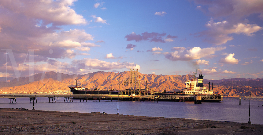 Tanker moored on the Israel side of the Gulf of Aqaba, near Eilat, Israel, with the sunlit rugged mountains of Jordan behind