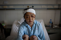 24 year old Dong Yuanyuan recovers in the Number 2 Hospital in Urumqi. She is an air stewardess teacher who was beaten up with her husband on a bus and left unconscious by a Uighur mob. She is now meant to be on her honeymoon with her husband, who has been missing since they were attacked and beaten. Ethnic violence between the Uighur and Han Chinese erupted in the city a few days earlier..