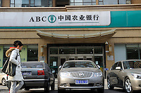 Chinese young couple walking past a branch of Agricultural Bank of China, in Beijing, China. Agricultural Bank founded in 1951, also known as AgBank, is one of the 'Big Four' banks in PRC, its headquarters in Beijing and has branches throughout mainland China, and also Hong Kong and Singapore..