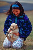 Young girl happily holding her golden retriever puppy.
