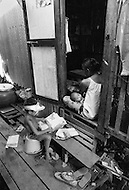A child is making paper boxes for selling peanuts in the streets of Bangkok, Thailand  - Child labor as seen around the world between 1979 and 1980 – Photographer Jean Pierre Laffont, touched by the suffering of child workers, chronicled their plight in 12 countries over the course of one year.  Laffont was awarded The World Press Award and Madeline Ross Award among many others for his work.