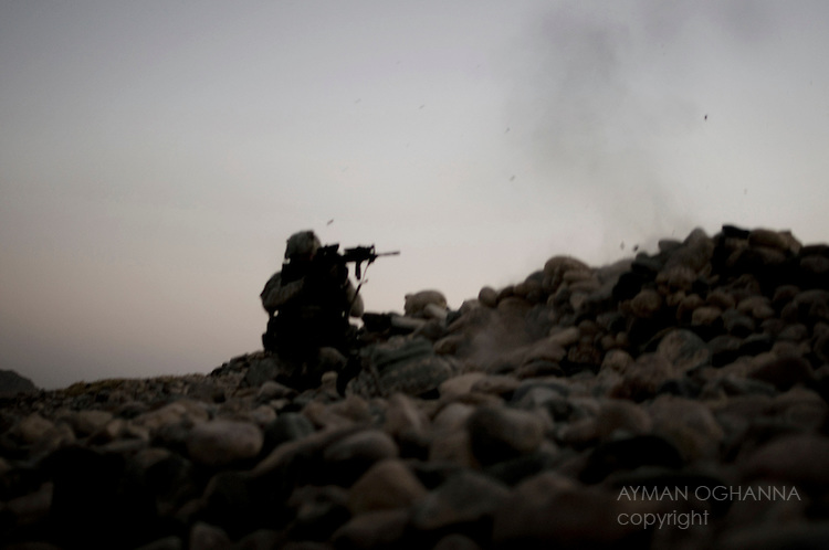 LT Eric Fitzgerald returns fire after being engaged by rocket propelled grenades and small arms fire from a compound on the banks of the Arghandab river, Kandahar province, Afghanistan...The soldiers are part of HAMKARI, NATO forces effort to take on the Taliban in its provincial birthplace of Kandahar.