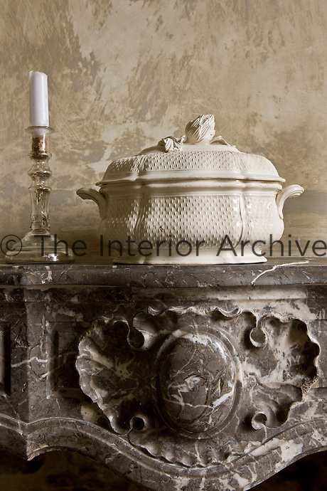 An English creamware vegetable dish is displayed with a mercury candlestick on the marble fireplace in the dining room