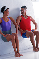 Man and woman doing post-workout stretching