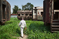 Nigeria. Enugu State. Enugu. Abandoned train at railway station. Old derelict rusty wagons on railroad tracks. The train has stopped running 25 years ago due to political reasons. An african man is walking on a path in between wagons. Enugu is the capital of Enugu State, located in southeastern Nigeria. 4.07.19 © 2019 Didier Ruef