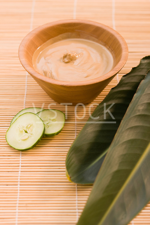 Mud mask, slices of cucumber and tropical plant leaves on bamboo mat