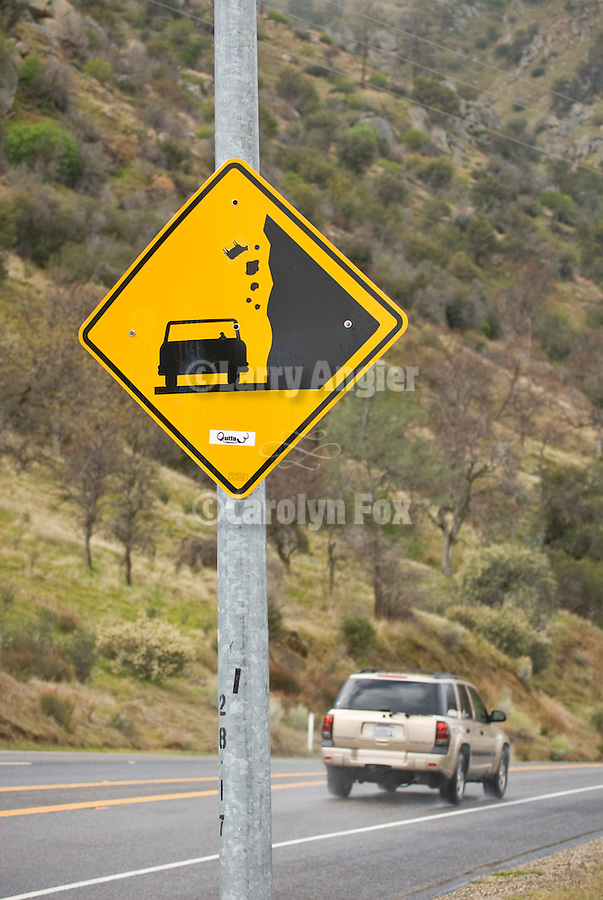 Caution: Falling Cattle, yellow diamond traffic sign warning of falling rock and cow (cattle) from the canyon walls along SR 178, Kern County, California.