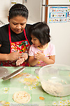 3 year old girl with mother in kitchen at home making tortillas