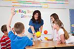 USA, Illinois, Metamora, Schoolchildren (8-9, 10-11) and female teacher with solar system model at science class
