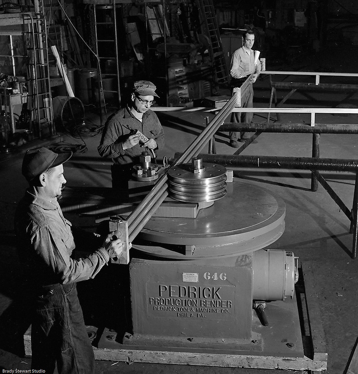 Client: The Pittsburgh Piping and Equipment Company<br /> Ad Agency: Pittsburgh Chamber of Commerce<br /> Contact: Mr. Emmerson<br /> Product: Fabricated Steel Pipe<br /> Location: Lawrenceville <br /> <br /> View of operator bending pipe with support of other workers with the new Pedrick Production Bender machine.  The manufacturer is the Pedrick Tool & Machine Company of Philadelphia Pennsylvania.  Photos were taken for the Pittsburgh Chamber of Commerce Local Business Display.<br /> <br /> Pittsburgh Piping and Equipment company started in 1928 and was a very successful fabricator and distributor of piping nationwide.