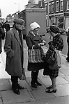 Two working class women in the street lighting up. One strikes a match from a box of matches for the others cigarette while her husband looks on. He is carrying the shopping bag and wearing a flat cap and neck scarf worn and tied in a traditional manner. They are going shopping in Roman Road market. East London England 1975