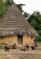 Africa, Liberia, Kpelle tribe: village scene: traditional cylindrical hut with conical thatch roof. Woman is making a fishing net.