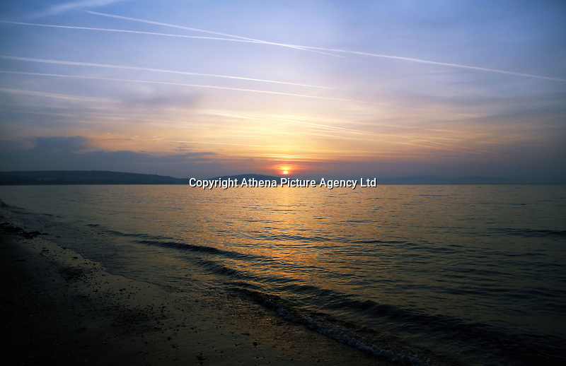 Pictured: The sun rises over Swansea Bay, as seen from West Cross in south Wales, UK. Wednesday 21 June 2017<br />Re: Summer Solstice