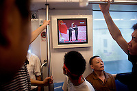 Seen on a screen in a subway train, government officials light the Olympic torch at the beginning of the Nanjing, China, leg of the 2008 Olympic Torch Relay.  The train was filled with people going to attend the Olympic Torch Relay as spectators.