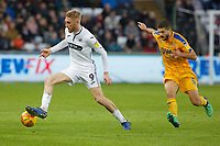 (L-R) Oli McBurnie of Swansea City chased by Sam Morsy of Wigan Athletic during the Sky Bet Championship match between Swansea City and Wigan Athletic at the Liberty Stadium, Swansea, Wales, UK. Saturday 29 December 2018
