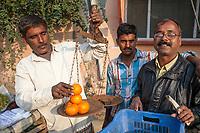 India, Dehradun.  Orange Vendor Weighing Oranges for a Customer.