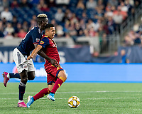 FOXBOROUGH, MA - SEPTEMBER 21: Sebastian Saucedo #23 of Real Salt Lake dribbles as Wilfried Zahibo #23 of New England Revolution defends during a game between Real Salt Lake and New England Revolution at Gillette Stadium on September 21, 2019 in Foxborough, Massachusetts.